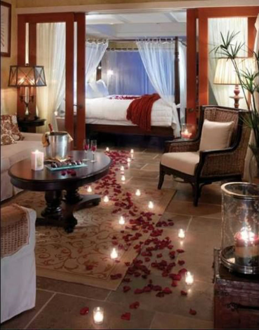 The petals path with the candles lighting the way towards the bed is incredibly romantic. Image Source: Pinterest