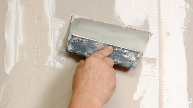 Plastering over dents and holes in drywall